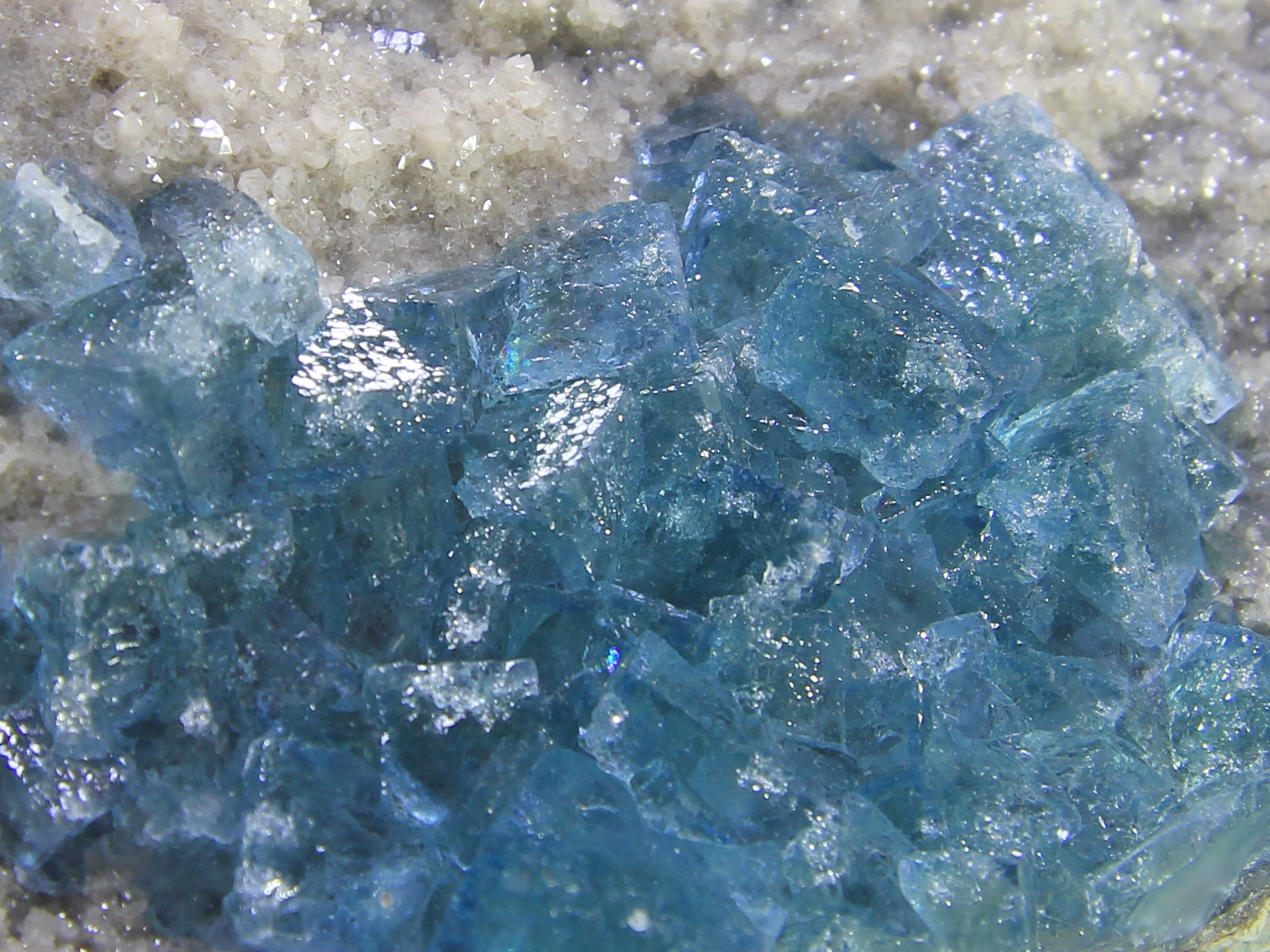 Sea blue fluorite on small crystallized quartz